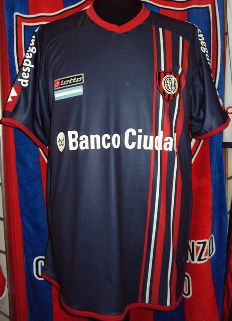 Cuervo Mania (Merchandising):        Camiseta Alternativa Azul Lotto 2014 Banco Ciudad